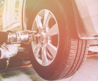 Close up of mechanic hands with pneumatic wrench changes wheel on car Royalty Free Stock Image