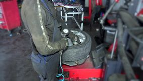 Close up of mechanic inflating tire on wheel in workshop stock video footage