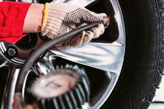 Close up of mechanic`s hand in glove checking the air pressure o Stock Photo