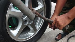 Mechanic twists the nuts on the wheel stock footage