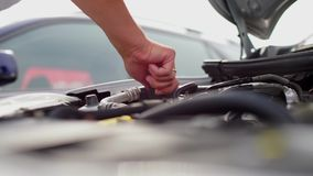 Mechanic unscrews and spins the cap of a car engine fluid. Close-up mechanic unscrews and spins the cap of a car engine fluid stock footage
