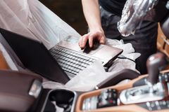 Close-up of mechanic using digital laptop while examining car engine in garage. connect the sensor connector to the car.  Stock Photos