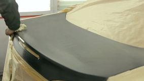 Mechanic seals the machine with protective paper before painting the rear hood. A close-up of a mechanic wiping a polished hood of a car before painting with a stock video footage