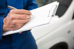 Close up of mechanic writing on clipboard Royalty Free Stock Photos