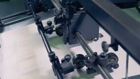 Close up of mechanical wheels and rollers pressing and stabilizing moving paper sheets stock video footage