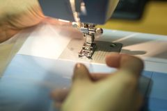 Close up mechanism of sewing machine foot with needle and thread stock photo