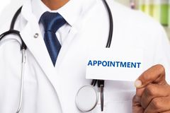Close-up of medic holding appointment card. Close-up of indian male medic or doctor holding blue appointment text on white business card stock image