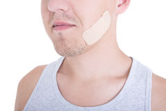 Close up of medical adhesive plaster on male face isolated on wh Royalty Free Stock Photography