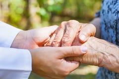 Trembling elderly hands. Close up medical doctor holding elderly female`s trembling hands Stock Photos