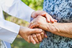 Shaking elderly hands. Close up medical doctor holding senior woman`s shaking hands, Parkinson disease Royalty Free Stock Images