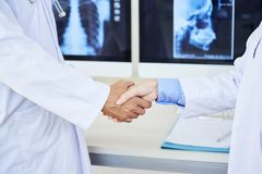 Doctors shaking hands at hospital stock image