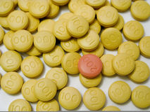 Close up of medicine. Yellow round tablets with 100 embossed on them with one lone red pill with 200 Stock Photography
