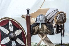 Close up of medieval knight equipment in old sleeping tent. Metal helmet, shield, sword stock image