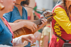 Close-up of medieval musicians body parts and guitar Stock Images
