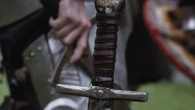 Close up of a medieval sword handle. Swords handle with a mans hand on the background stock video