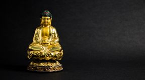 Close up of Meditating Golden Buddha statue on black background stock images