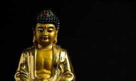 Close up of Meditating Golden Buddha statue on black background stock image