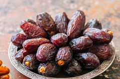 Close up of medjoul - dried dates or kurma in a vintage plate. Close up of medjoul - dried dates or kurma in a vintage plate rusty background Stock Image