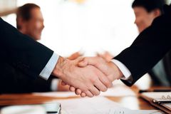Close up meeting with chinese businessmen in restaurant. Men are shaking hands. Royalty Free Stock Photography