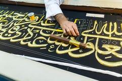 Close up men create Islamic calligraphy koran verses Royalty Free Stock Images