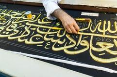 Close up men create Islamic calligraphy koran verses Royalty Free Stock Photos
