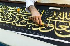 Close up men create Islamic calligraphy koran verses Royalty Free Stock Photo