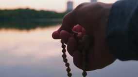 Close-up, Men Hand Holds Little Rosary, Evening Prayer on the River Bank. Close-up, Men Hand Holds Small Wooden Rosary, Evening Prayer on the River Bank stock footage