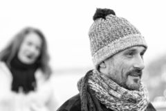 Close up man portrait in knitted hat. Happy guy black and white winter portrait stock photos