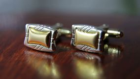 Close-up of men`s cufflinks for shirt on a table. stock footage