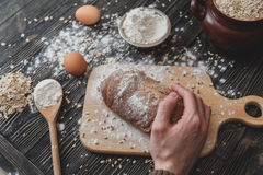Close-up of men`s hands on black bread with flour powder. Baking and patisserie concept. Close-up of men`s hands on black bread with flour powder. Baking and royalty free stock photo