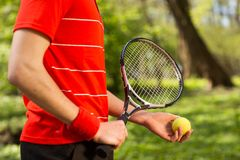 Close up of men`s hands hold a tennis racket and ball on the green background. Sport concept.  stock photos
