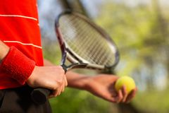 Close up of men`s hands hold a tennis racket and ball on the green background. Sport concept.  stock images