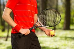 Close up of men`s hands hold a tennis racket and ball on the green background. Sport concept.  royalty free stock photography
