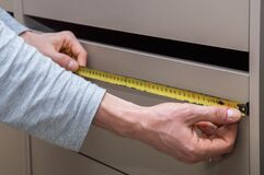 Close up. Men`s hands measure the length of shelves in a dresser with a tape measure