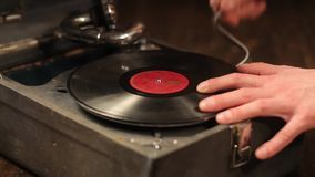 Playing vinyl records on a retro gramophone, potefone. Close-up. Men`s hands put a vinyl record and start a gramophone. HD stock footage