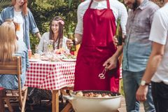 Close-up of men standing and talking over a grill with shashliks. Beautiful woman sitting by a birthday party table in royalty free stock images