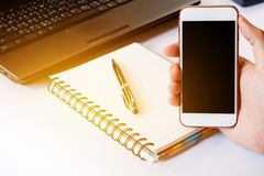 Close up of a men using smart phone with blank mobile and calcul. Ator, pen, notebook. Smart phone with blank screen with clipping path. Hand using a white smart Stock Image
