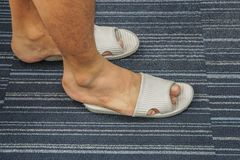 Men wear too tight sandal on his feet in the house. Close up men wear too tight sandal on his feet in the house Stock Images