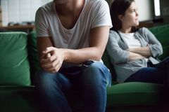 Unhappy couple sitting on couch at home stock photography