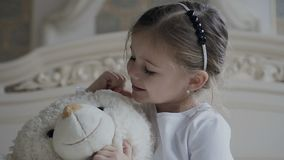 Close-up A menina senta-se em um tapete branco na cama e abraça-se um brinquedo macio do urso Menina bonita e seu brinquedo macio video estoque