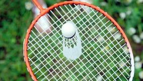 Close-up, mening van hierboven Een kind, een jongen, houdt een shuttle op een badmintonracket stock videobeelden