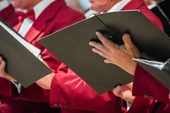 Mens choir performing in a cathedral. Close up of mens choir members holding singing book while performing in a cathedral in Rochester, Kent, UK stock photo
