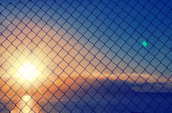 Close up of mesh fence against the blurred sunset sky. Abstract blue orange background Royalty Free Stock Photos