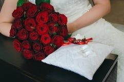 Close-up met bruid en bruidegomhanden en boeket Bruid, die een huwelijksboeket van bloemen houden Huwelijks zilveren ringen Bruid royalty-vrije stock afbeeldingen
