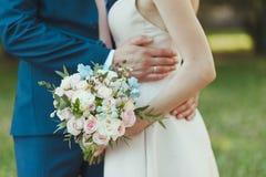 Close-up met bruid en bruidegomhanden en boeket Bruid, die een huwelijksboeket van bloemenrozen houden De gouden ringen van het h stock foto