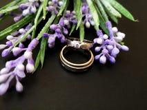 Close-up met trouwringen met de mooie achtergrond van de rozenbloem royalty-vrije stock fotografie