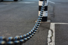 Close-up of metal chain vanishing in background. Hanging chain as safety barrier Stock Photos