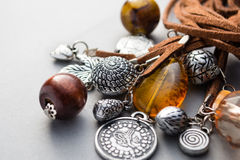 Close up of metal charms and wood beads on gray Royalty Free Stock Photos