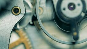 Close up of metal cogs moving in a watch mechanism