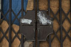Close up of a metal fence with wooden wall.  royalty free stock images